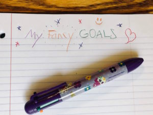 "Note page with a kid's handwriting says ""My Fancy Goals"" in many colors and with stars and hearts."